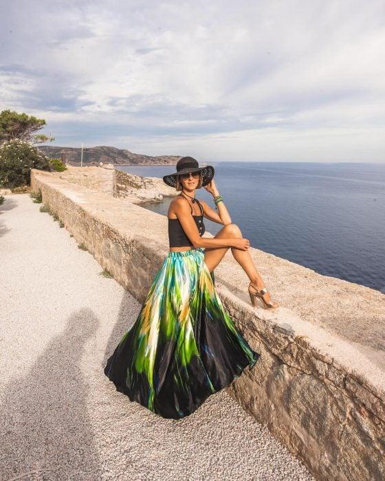 Chica en la playa usando un un sombrero negro, lentes, top negro y falda larga de satín de colores