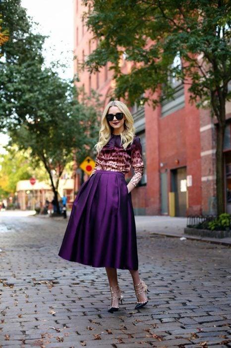 Chica rubia en calle empedrada usando blusa morada de animal print y falda midi de satín color morado