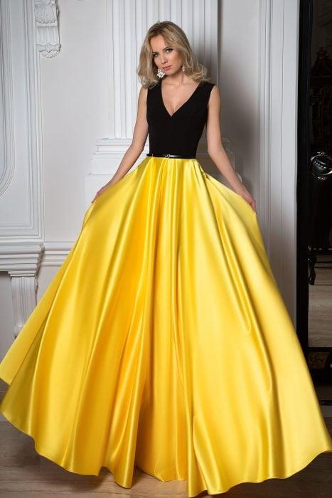 Chida rubia usando un top sencillo negro y falda larga de satín amarilla