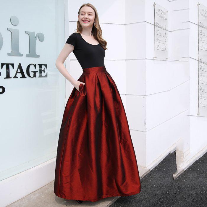 Chica de cabello castaño claro y largo sonriendo y vistiendo una falda larga de satín roja con un top sencillo negro