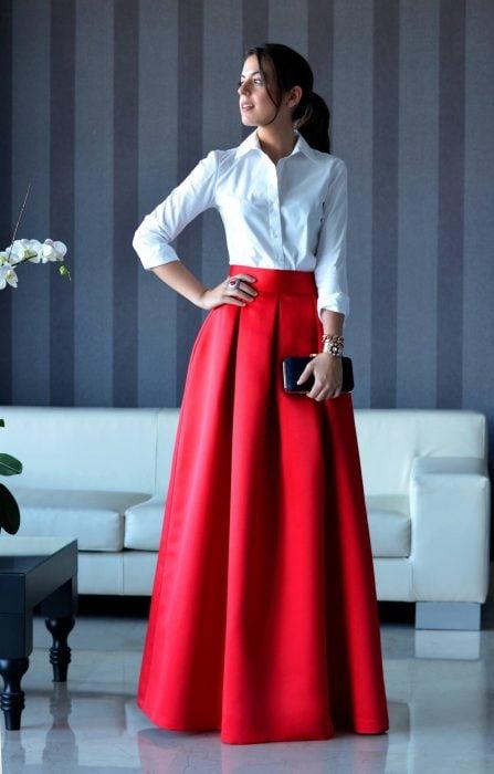 Chica de cabello castaño con una coleta vestida con una falda larga de satín roja y una blusa blanca formal