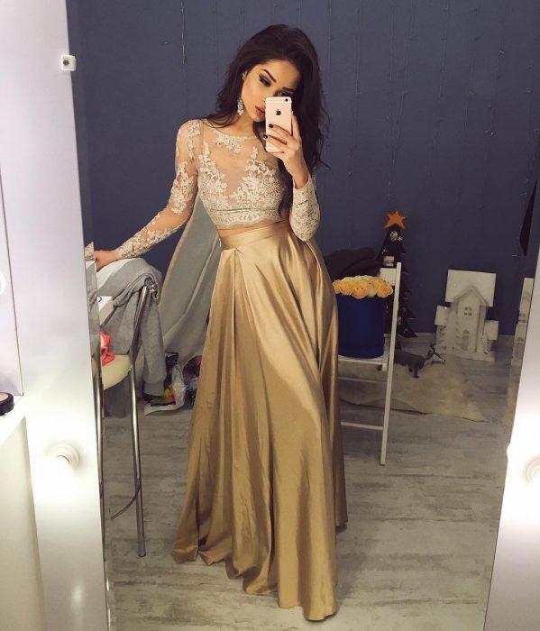 Chica de cabello castaño y largo usando un top de encaje y una falda larga de satín dorada tomándose una selfie