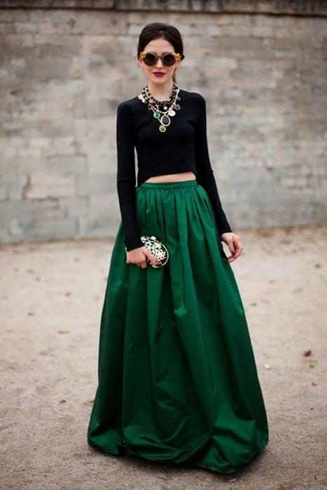 Chica con el cabello recogido usando lentes redondos, collar grande, blusa negra de manga larga y una falda larga de satín verde esmeralda