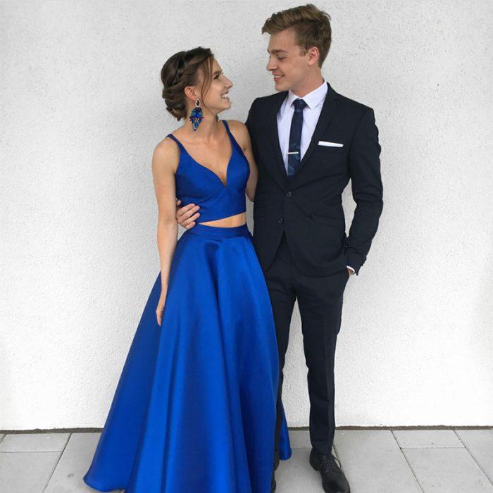 Pareja de novios posando para una foto de graduación vestidos con traje negro y top y falda de satín azul