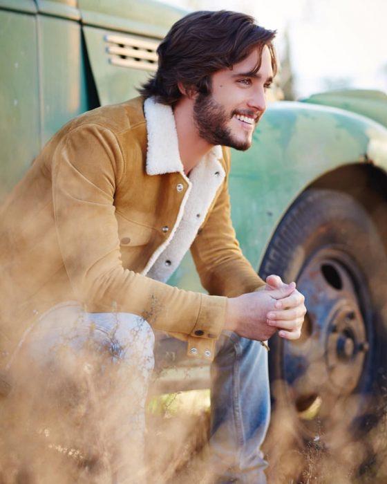 Diego Boneta, chico con chamarra color camello sentado en un carro y sonriendo