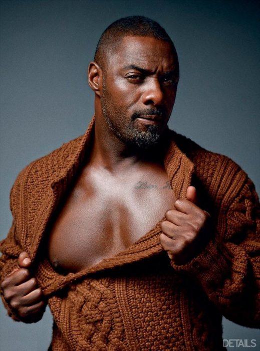 Idris Elba, hombre moreno, pelón con suéter café tejido