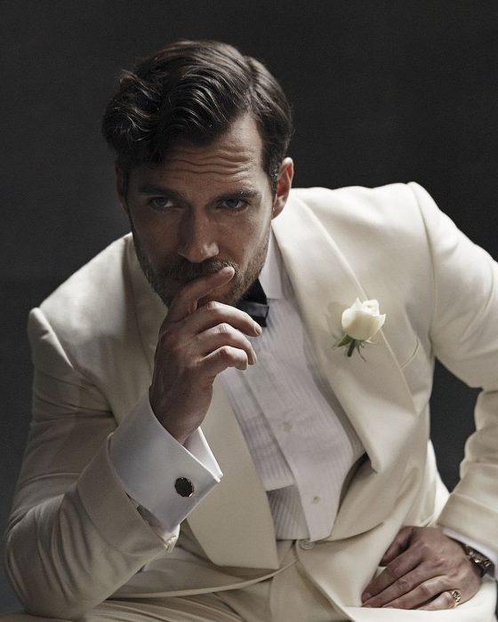 Henry Cavill, hombre de cabello corto con traje blanco y una mano en la boca