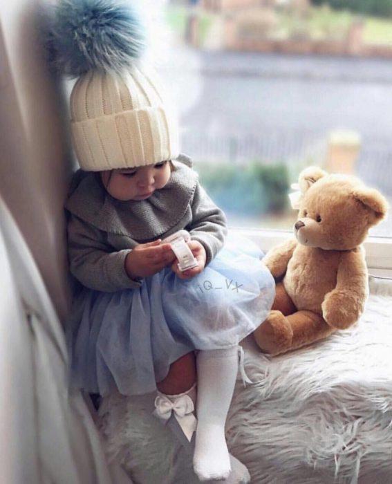 niña con gorro y peluche en la ventana