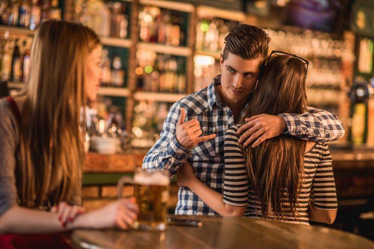 Hombre de camisa de cuadros abrazando a una mujer y hablándole a otra por la espalda