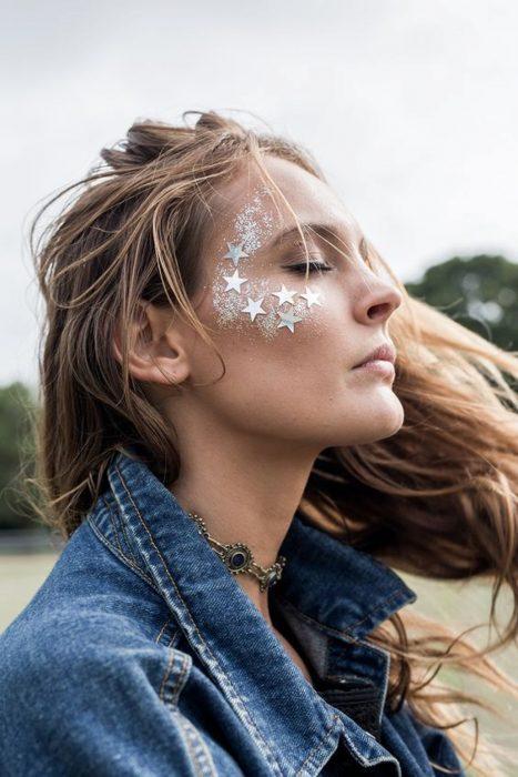 Chica rubia con glitter de estrellas en los pómulos