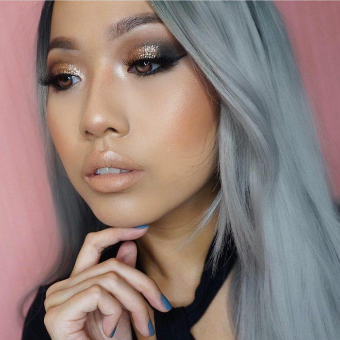 Chica de cabello gris con maquillaje de ojos con glitter