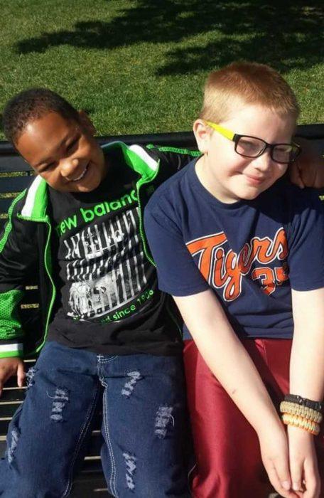 Dos chicos que son mejores amigos sentados en la banca de un parque