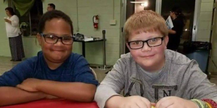 Dos chicos con lentes que son mejores amigos sentados en una mesa