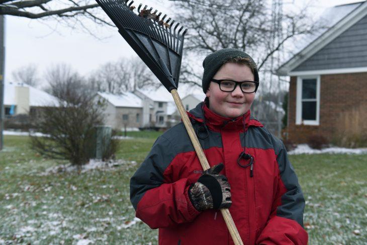 Chico usando lentes, gorro y chamarra para el frío sosteniendo una escoba para hojas