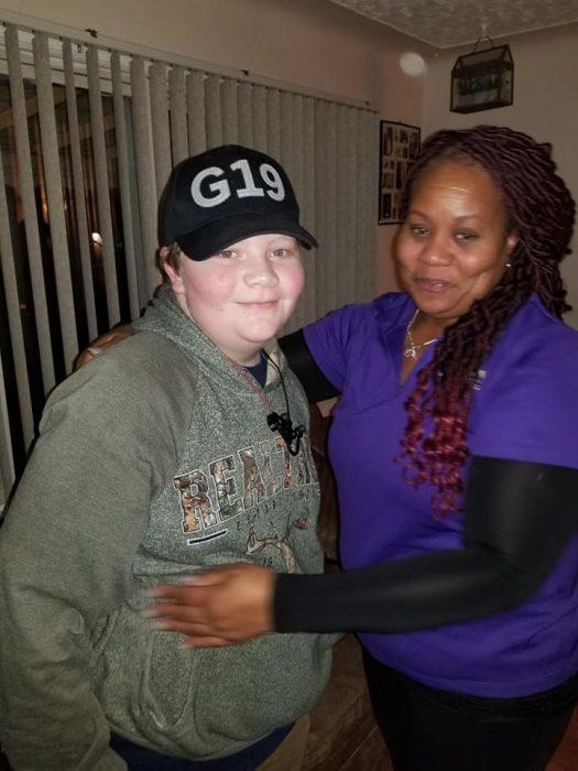 Chico con una gorra y sudadera abrazando a una mujer afroamericana de rastas y con blusa morada