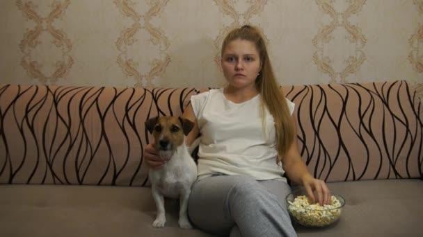 Niña comiendo palomitas junto a su perrito