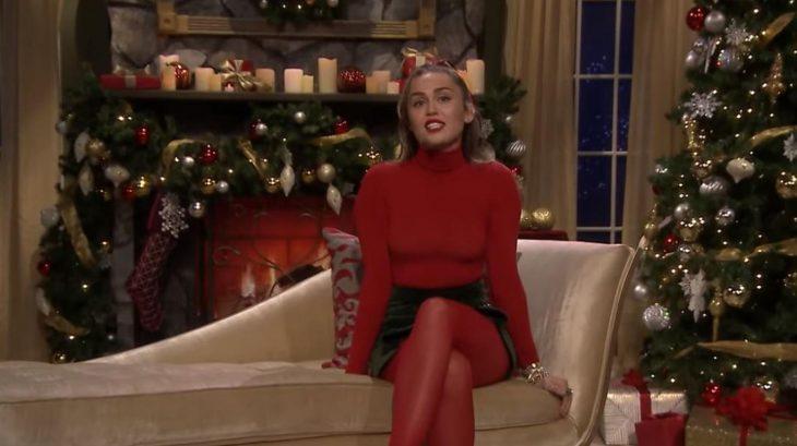 chica con traje rojo cantando en el sofá