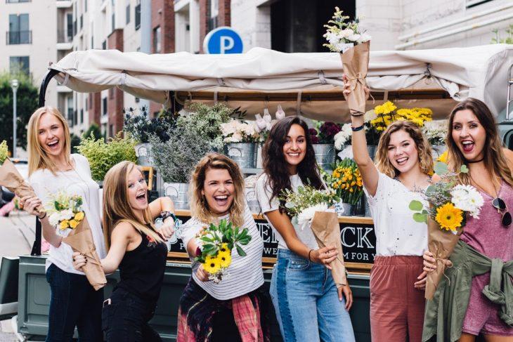 grupo de chicas felices cargando flores