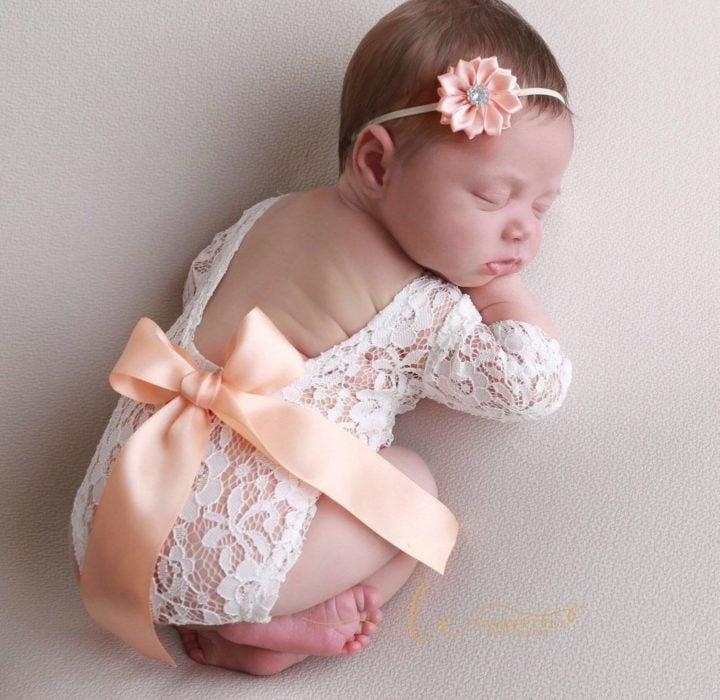 Bebé niña recostada sobre un puff durante una sesión de fotos usando un pañalero de encaje en color blanco con un moño durado