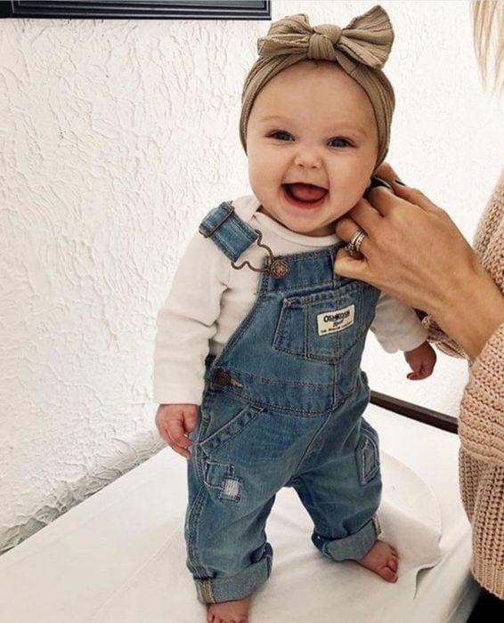 Bebé niña sonriendo mientras su mamá le coloca la ropa