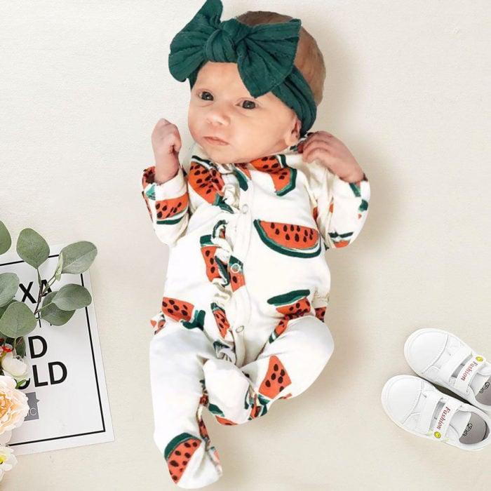 Bebé niña recostada sobre una cama durante una sesión de fotos
