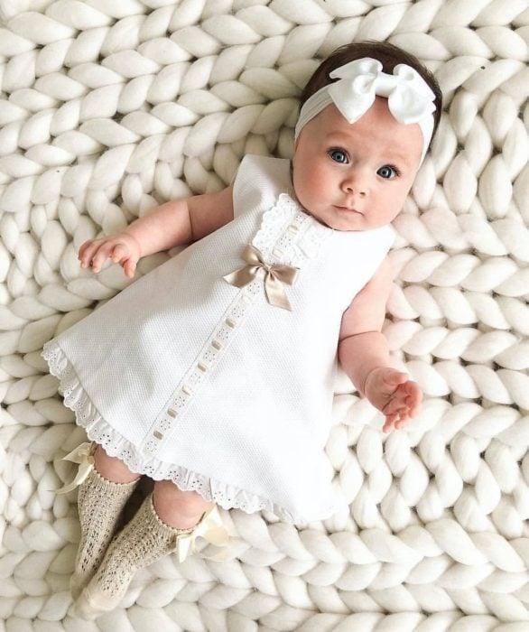 Bebé niña recostada en una manta tejida, usando un vestido de color blanco con un moñito blanco y calcetitas doradas