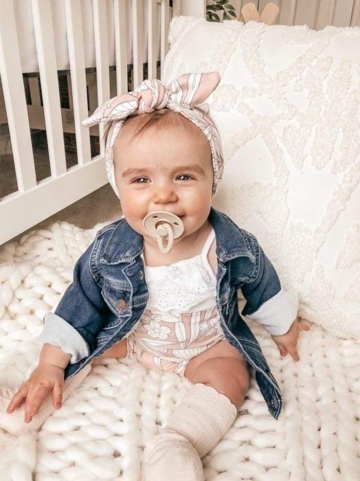 Bebé niña sentada en su cuna usando una camisetita de mezclilla con una bandita en la cabeza
