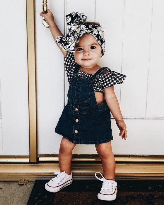 Bebé niña sujetada e una pared mientras usa un jumper de mezclilla, bandita en la cabeza y converse