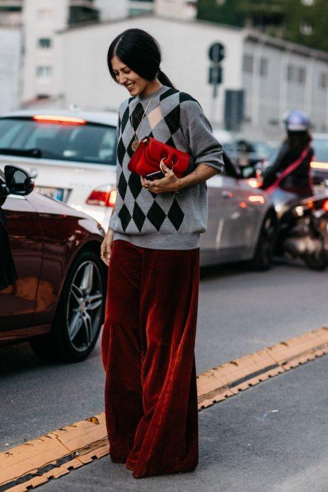 Chica de cabello agarrado en coleta con suéter amplio de rombos y pantalón holgado de terciopelo rojo
