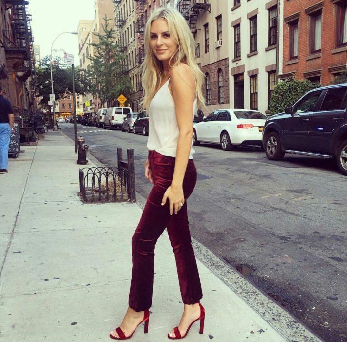 Chica rubia caminando en la calle con blusa de tirantes blanca, pantalón rojo de terciopelo y tacones rojos