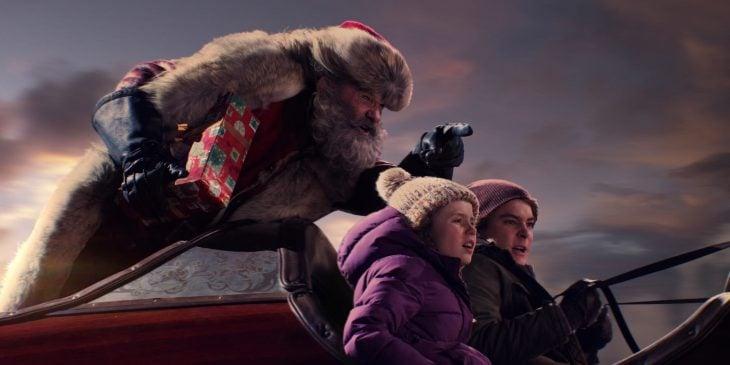 Santa Claus volando en el trineo con dos niños con chamarras