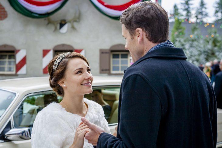 Chica con chamarra blanca y tiara sonríe a un hombre