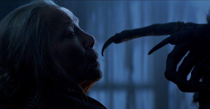 Mujer anciana con casa asustada frente a un demonio que la señala