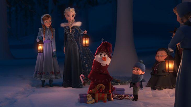 Muñeco de nueve abrigado con dos mujeres con abrigos largos mirándolos