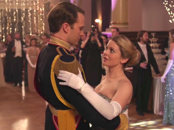 Príncipe con traje elegante bailando con una mujer rubia de vestido y guantes largos y blancos