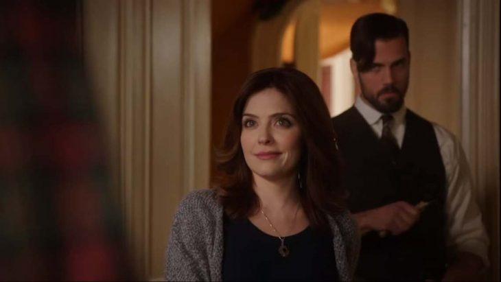Mujer peliroja sonriendo mientras atrás hay un hombre de barba, chaleco elegante y corbata