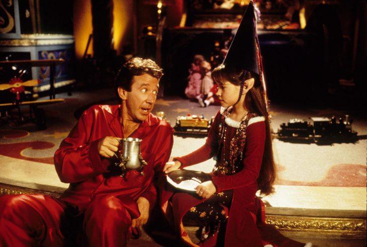 Hombre vestido de rojo tomando una bebida caliente con una elfa con vestido rojo y gorro de Navidad