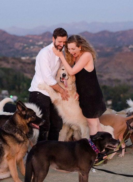 pareja d enovios siendo abrazados por un perro