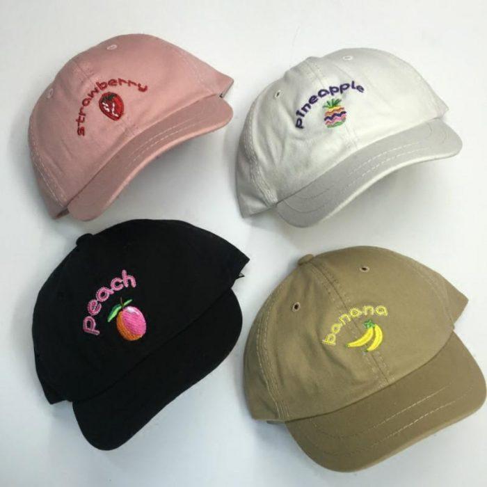 cuatro gorras de colores y frutas
