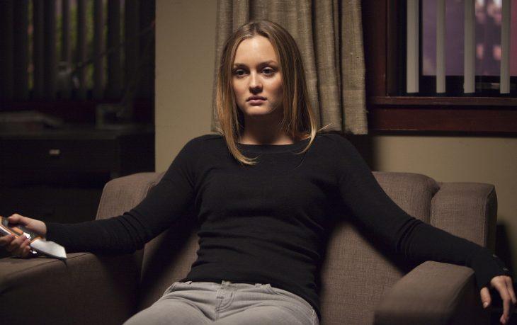 Chica de cabello castaño y lacio de blusa negra sentada en un sillón con cara enojada