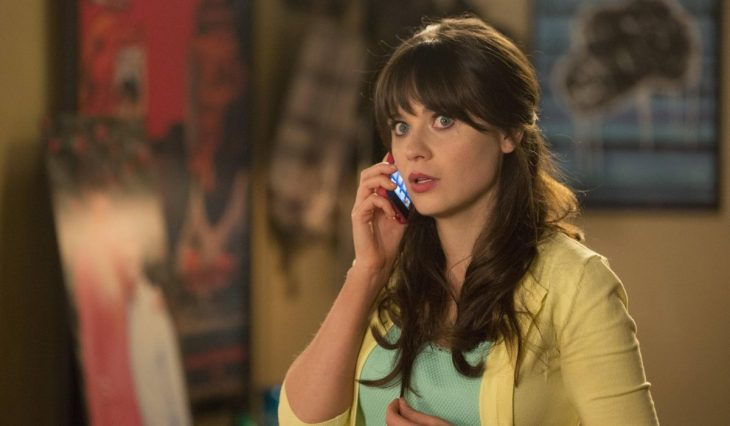 Chica de cabello castaño con blazer amarillo hablando por celular