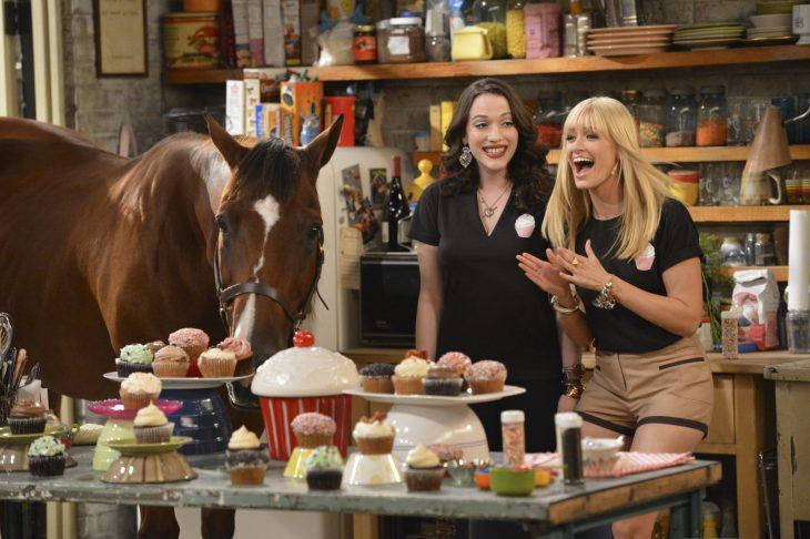 Chica rubia y castaña cocinando cupcakes en la cocina con un caballo