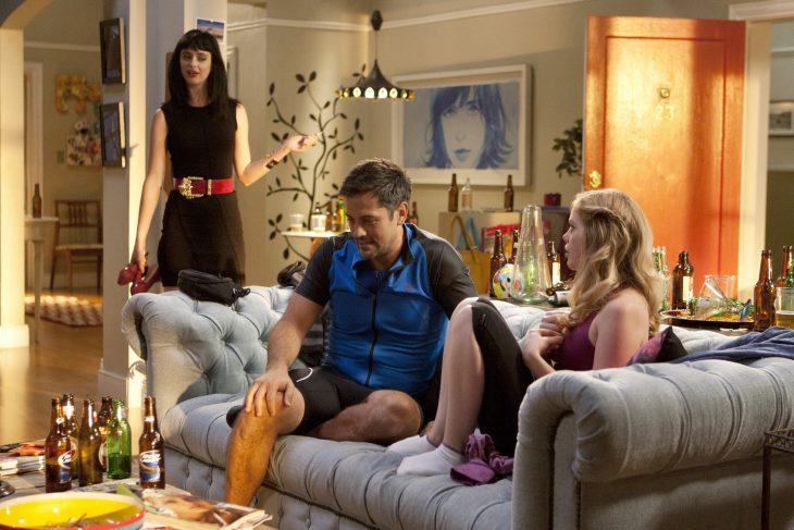 Chica y chico sentados en el sillón mientras otra chica de cabello negro y vestido negro los mira