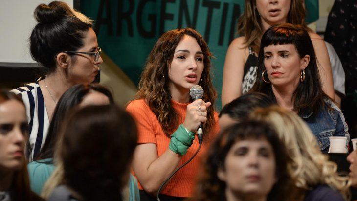Thelma Fardín, mujer de blusa anaranjada y cabello chino hablando por un micrófono rodeada de más mujeres