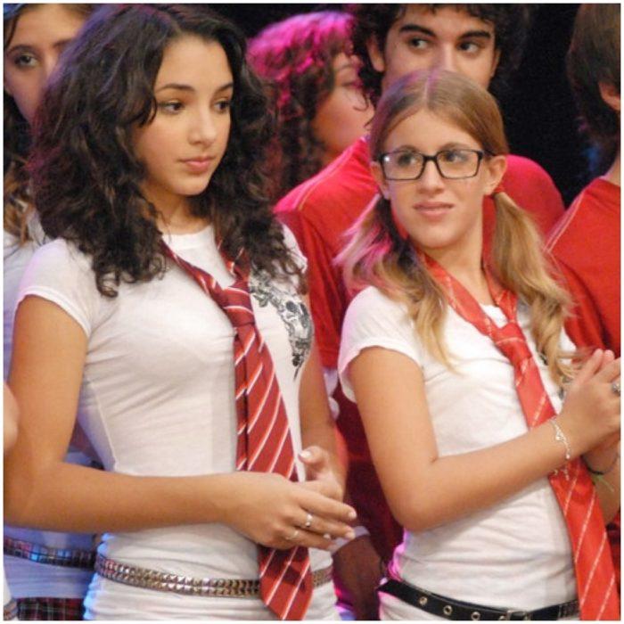 Thelma Fardín en la serie infantil Patito feo vestida con blusa blanca y corbata roja al lado de su amiga