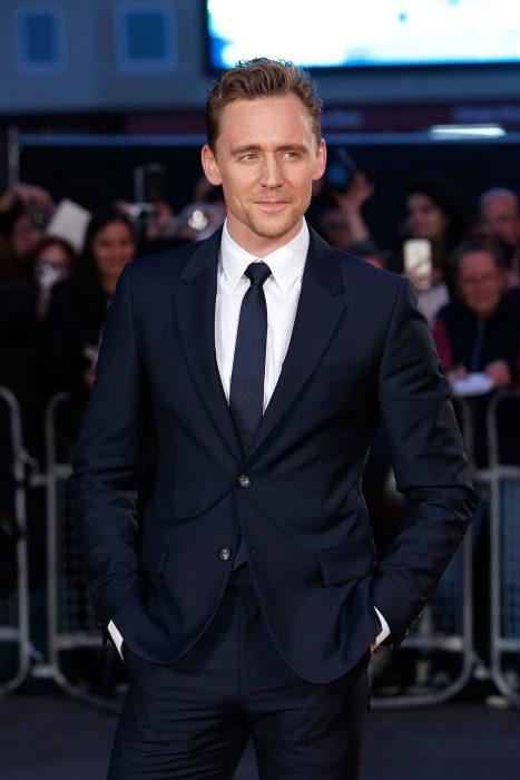 Chico de cabello castaño claro y ojos azules posando con un traje azul marino con corbata