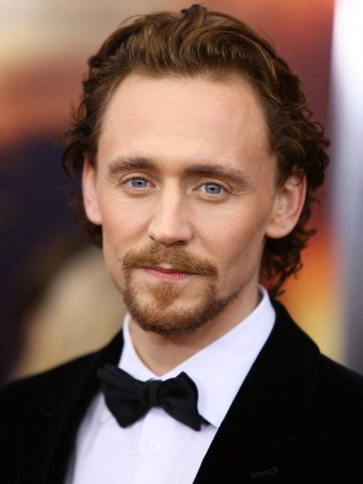 Chico de cabello castaño, barba y ojos azules con traje de gala y moño