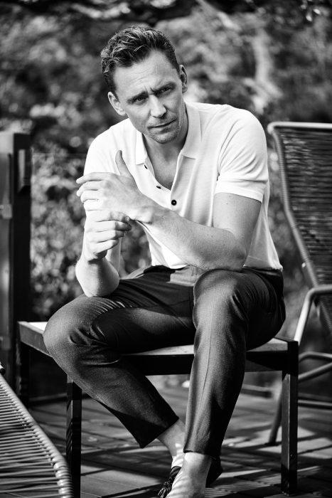 Fotografía de hombre en blanco y negro con camisa tipo polo blanca, pantalones de vestir sentado en una silla