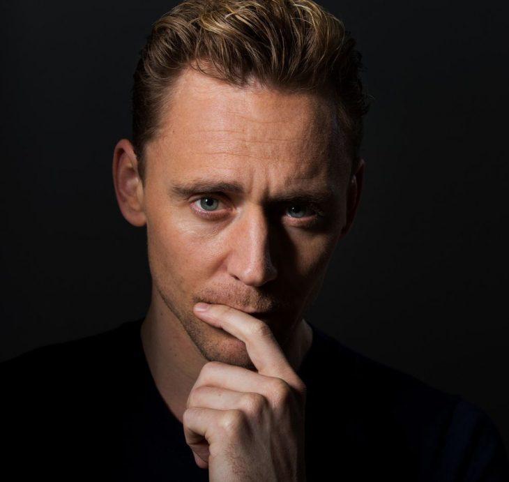 Chico de cabello castaño rojizo y ojos azules con la mano en el mentón
