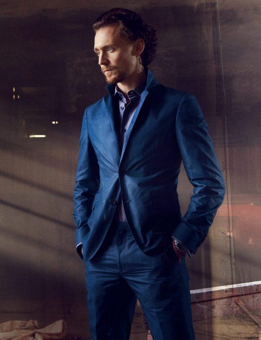 Chico de cabello castaño con traje azul con las manos metidas en los bolsillos